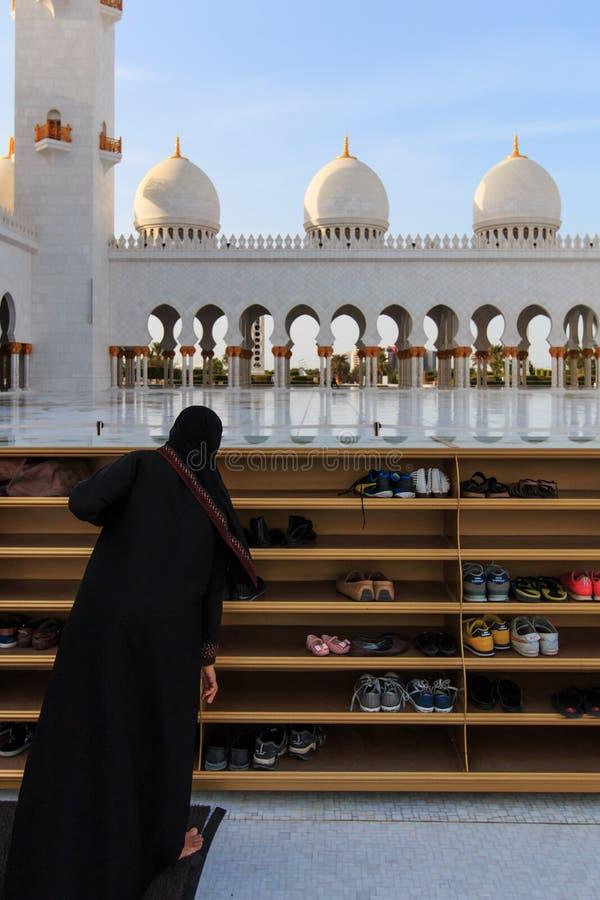 Mujer que saca sus zapatos antes de inscribir a Sheikh Zayed Grand Mosque fotografía de archivo libre de regalías