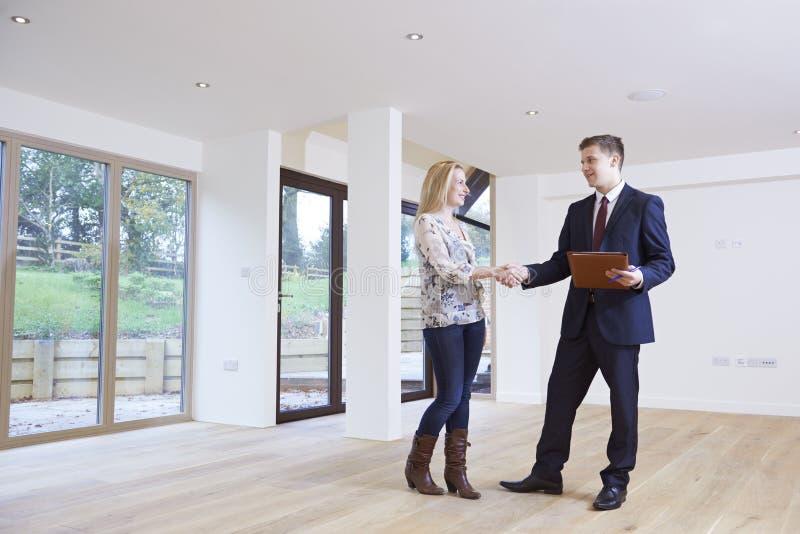 Mujer que sacude las manos con el agente de la propiedad inmobiliaria In New Home fotos de archivo
