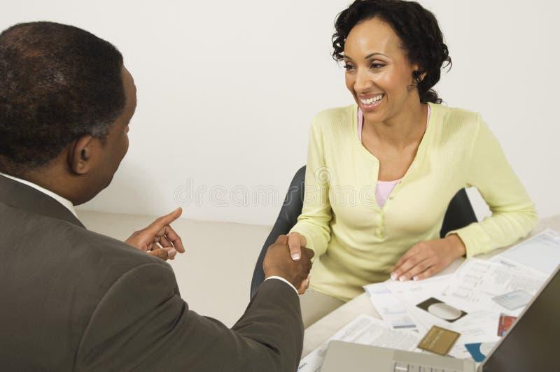 Mujer que sacude las manos con el consejero financiero fotos de archivo libres de regalías