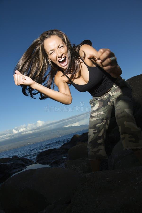 Mujer que sacude los puños por el océano. imagen de archivo libre de regalías