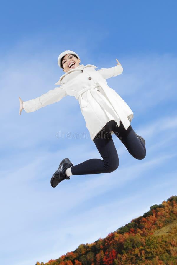 Mujer que salta en parque del otoño imagenes de archivo