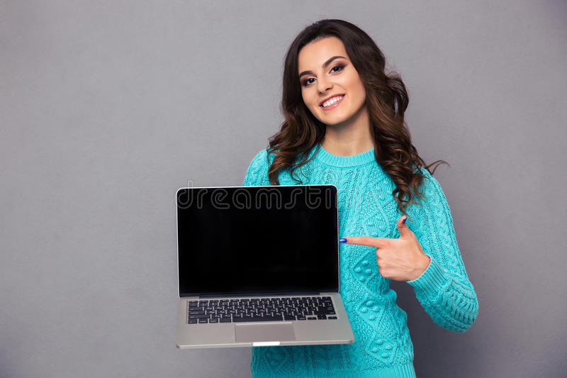 Mujer que señala el finger en la pantalla de ordenador portátil en blanco fotografía de archivo