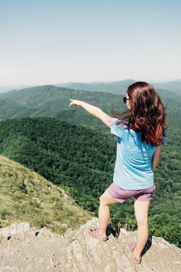 Mujer que señala en las montañas en verano fotografía de archivo libre de regalías