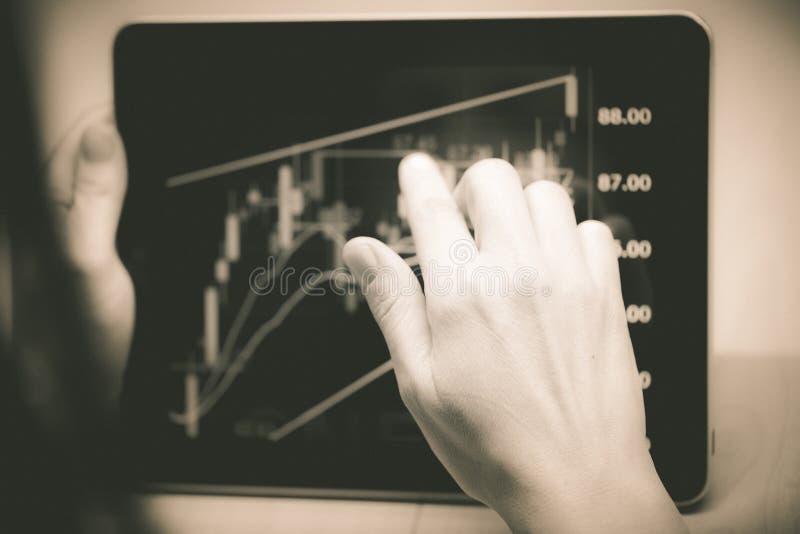 Mujer que señala en una carta común en una pantalla de la tableta fotografía de archivo libre de regalías