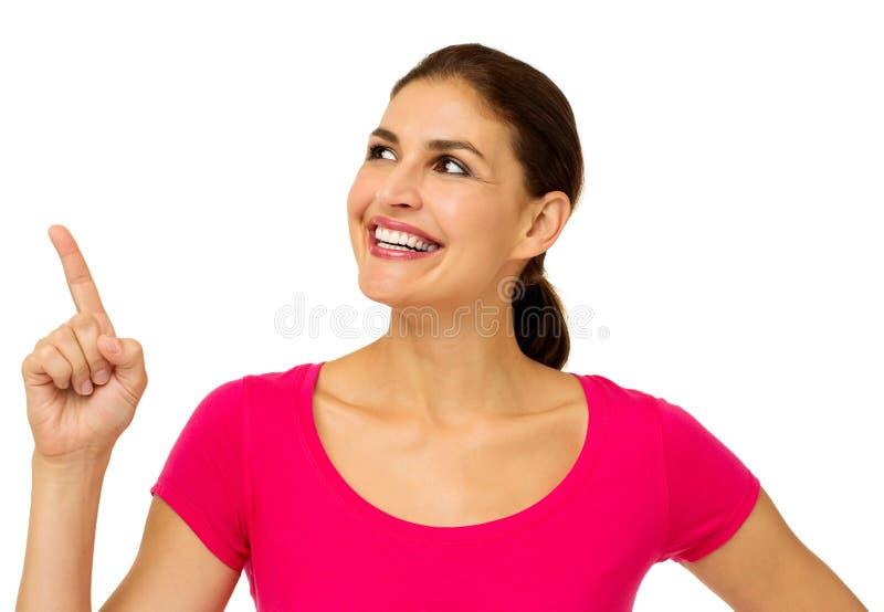 Mujer que señala hacia arriba sobre el fondo blanco foto de archivo libre de regalías