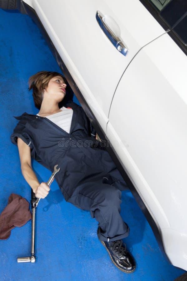 Mujer que se acuesta en el piso que trabaja en el coche en garaje del automóvil fotos de archivo