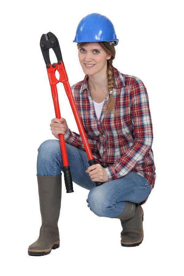 Mujer que se agacha con los cortadores de tornillo