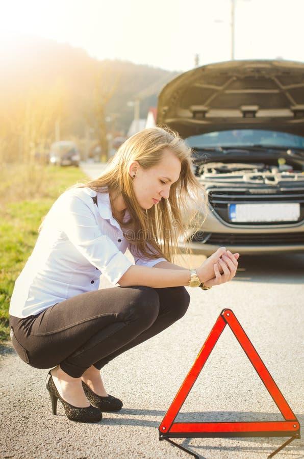 Mujer que se agacha en el camino Persona triste Coche dañado Fondo natural Accidente de tráfico imagen de archivo libre de regalías