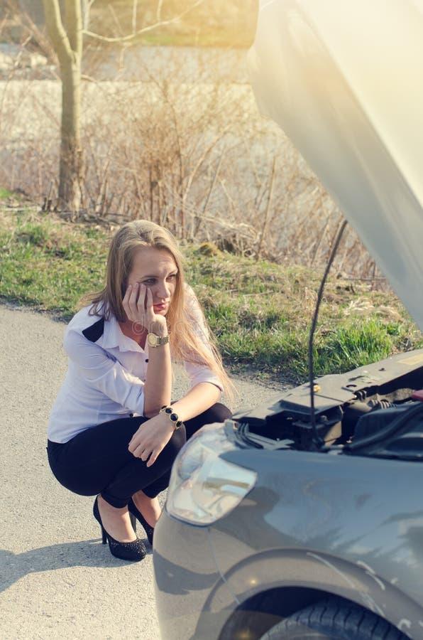 Mujer que se agacha en el camino Persona triste Coche dañado Fondo natural Accidente de tráfico fotografía de archivo