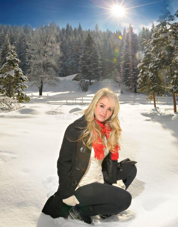 Mujer que se agacha en nieve imagen de archivo