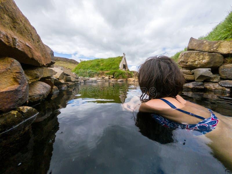 Mujer que se baña en una pequeña piscina caliente en Hrunalaug, Islandia imagenes de archivo