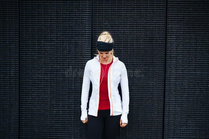 Mujer que se coloca al aire libre en la ropa de deportes que mira abajo imagen de archivo