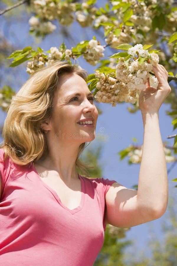 Mujer que se coloca al aire libre que celebra la sonrisa del flor imagenes de archivo