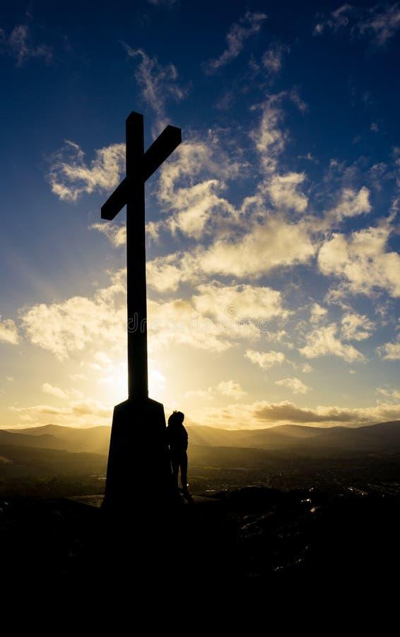 Mujer que se coloca al lado de cruz en la puesta del sol en Bray Head, Irlanda fotografía de archivo libre de regalías