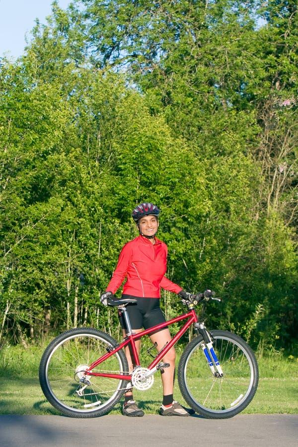 Mujer que se coloca al lado de la bicicleta - vertical fotografía de archivo libre de regalías