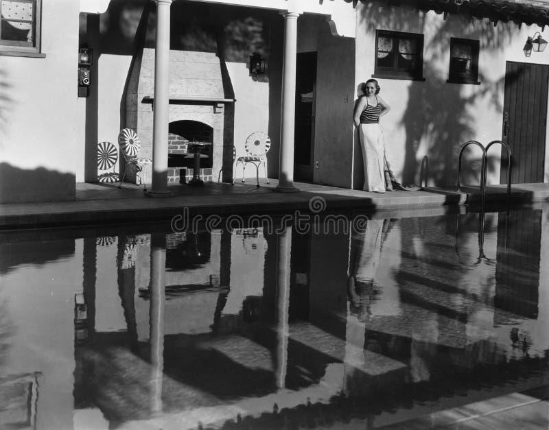 Mujer que se coloca cerca de piscina al aire libre (todas las personas representadas no son vivas más largo y ningún estado exist fotografía de archivo