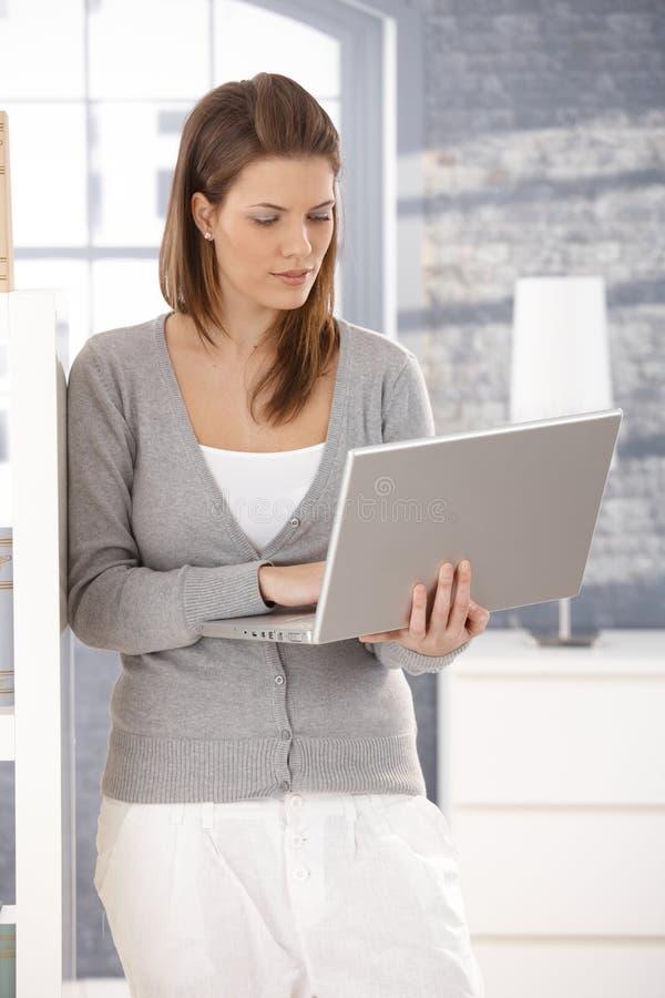 Mujer que se coloca con la computadora portátil en el país imagenes de archivo
