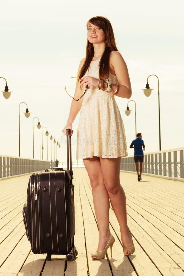 Mujer que se coloca con la maleta, embarcadero en fondo fotografía de archivo