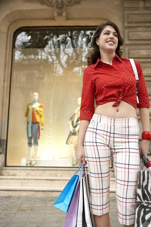 Mujer que se coloca con los bolsos de compras imagen de archivo libre de regalías