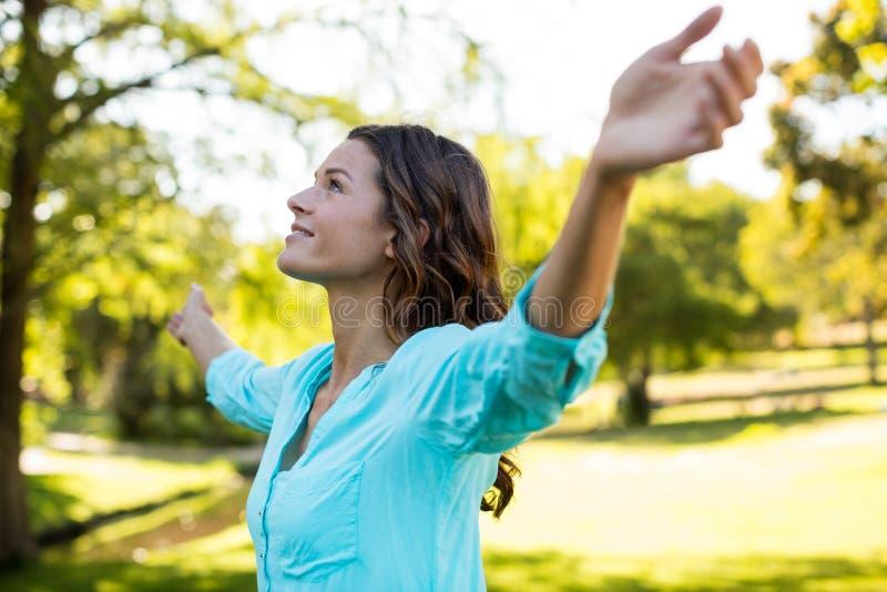 Mujer que se coloca con los brazos extendidos en parque foto de archivo libre de regalías