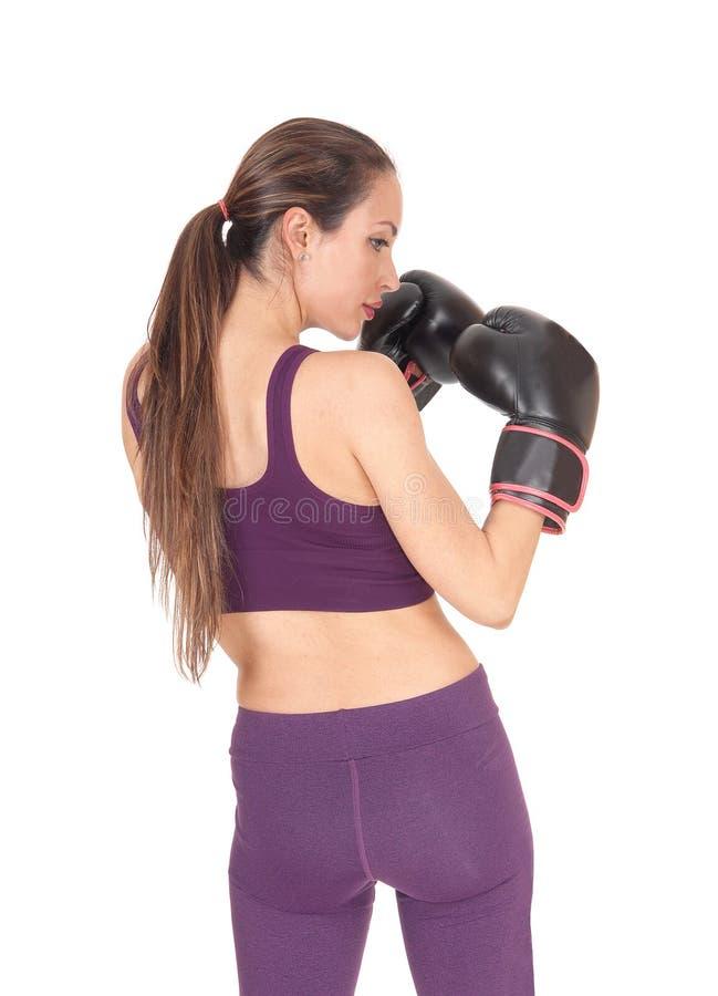 Mujer que se coloca de la parte posterior con los clavos del boxeo fotos de archivo