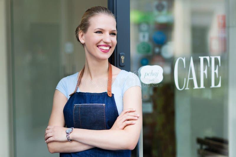 Mujer que se coloca delante de cafetería foto de archivo