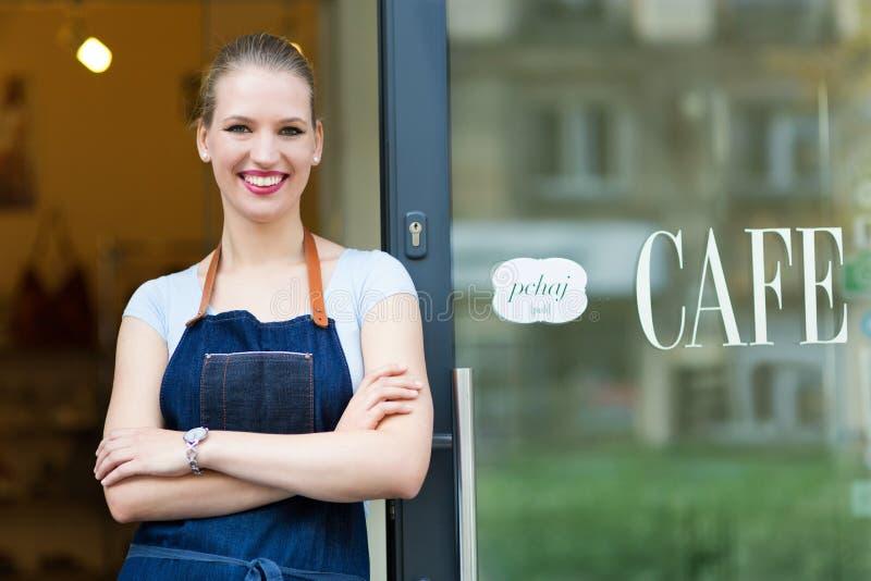 Mujer que se coloca delante de cafetería imagen de archivo libre de regalías