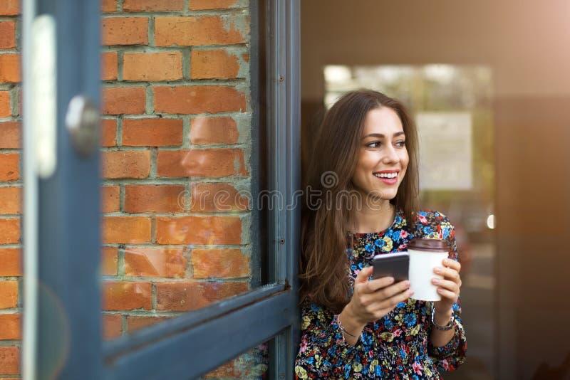 Mujer que se coloca delante de cafetería fotos de archivo