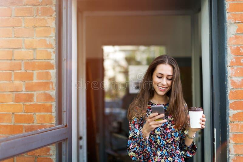 Mujer que se coloca delante de cafetería fotografía de archivo libre de regalías