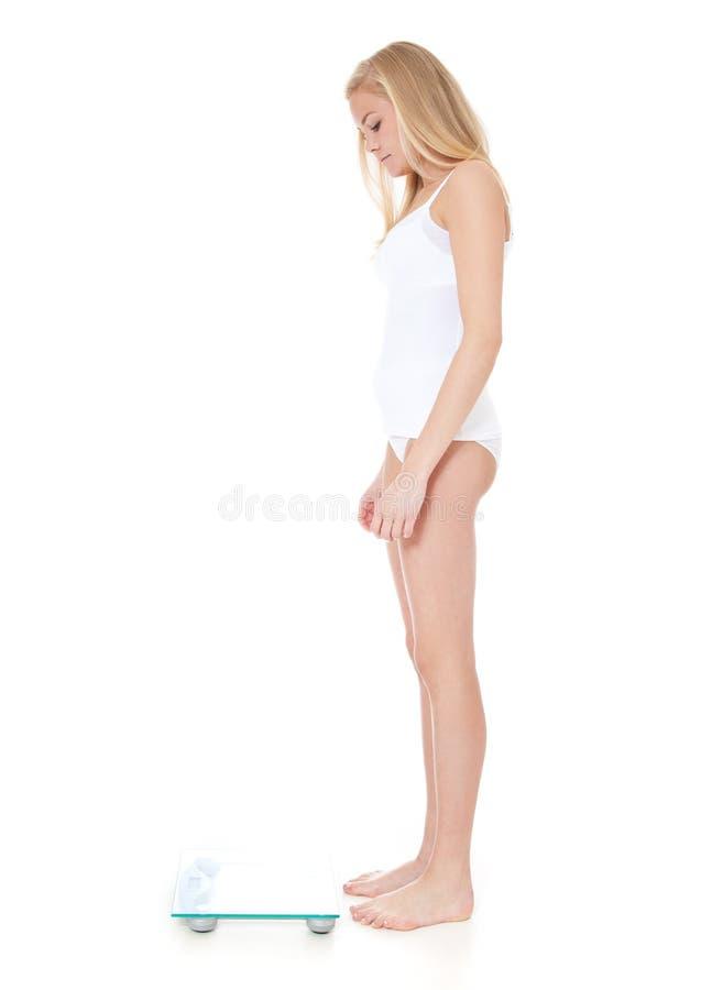 Mujer que se coloca delante de escala personal foto de archivo