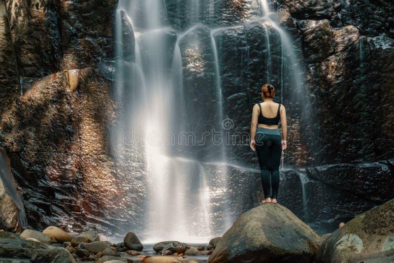 Mujer que se coloca delante de una cascada fotografía de archivo