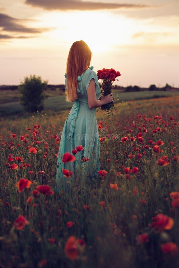 Mujer que se coloca en campo floreciente de la amapola fotografía de archivo libre de regalías