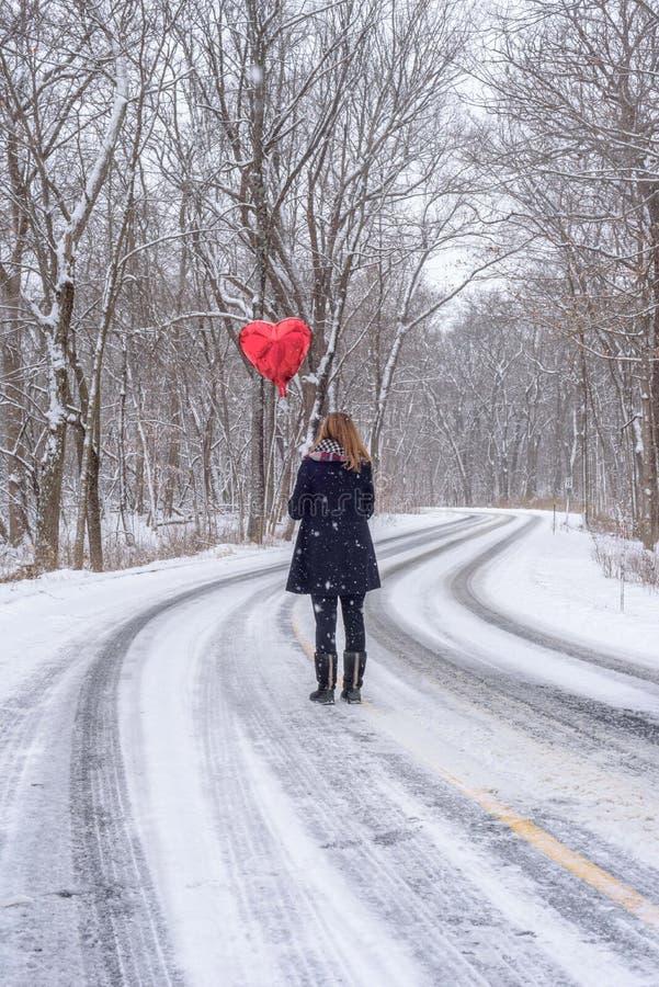mujer que se coloca en centro del camino enselvado nevado que lleva a cabo un r fotografía de archivo