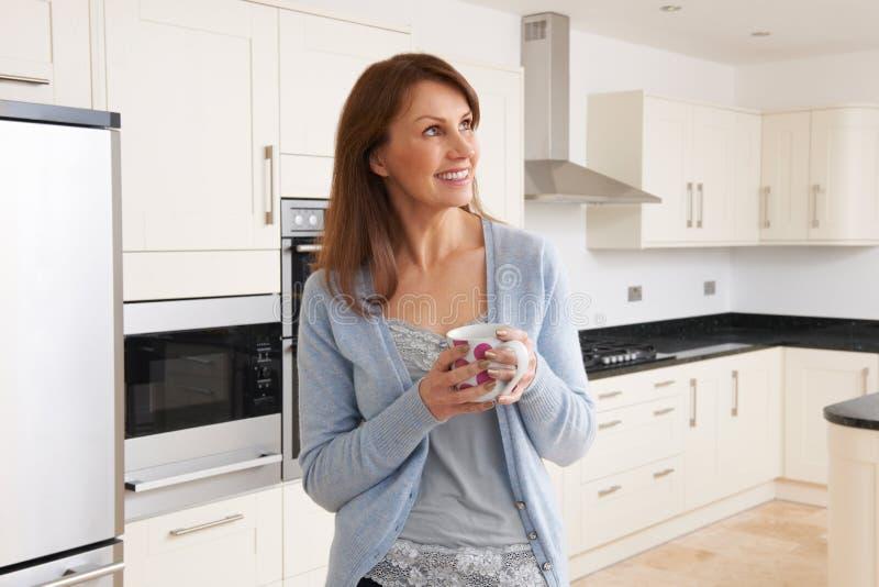 Mujer que se coloca en cocina cabida nuevo lujo foto de archivo
