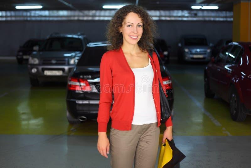 Mujer que se coloca en el estacionamiento subterráneo del coche fotografía de archivo libre de regalías