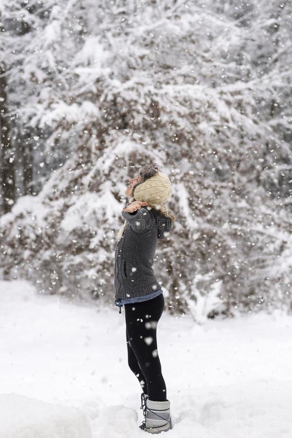 Mujer que se coloca en el medio de un snowf que da la bienvenida del arbolado nevoso imagen de archivo