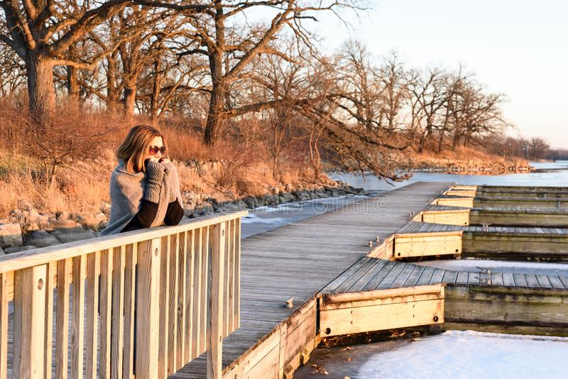 Mujer que se coloca en el puente de madera en invierno foto de archivo libre de regalías