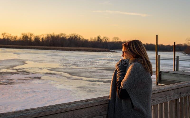 Mujer que se coloca en el puente sobre puesta del sol de observación del río congelado foto de archivo