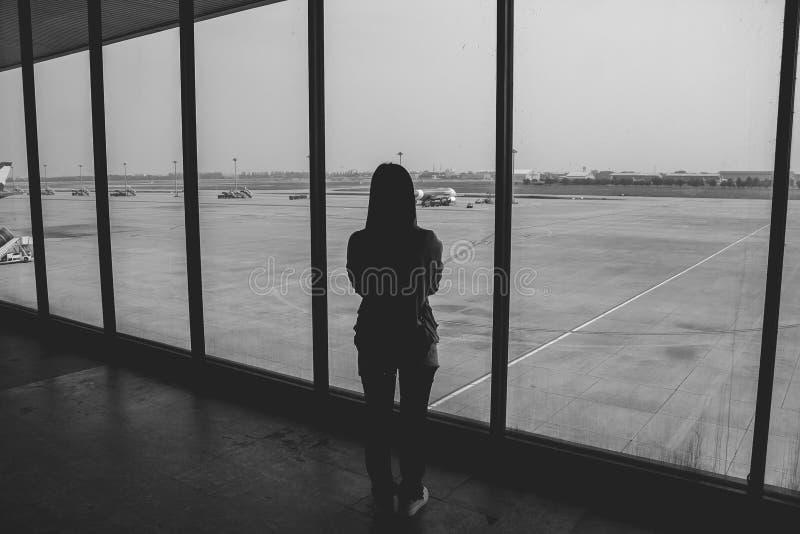 Mujer que se coloca en el terminal de aeropuerto y que mira los aeroplanos mientras que espera en la puerta de embarque imagen de archivo