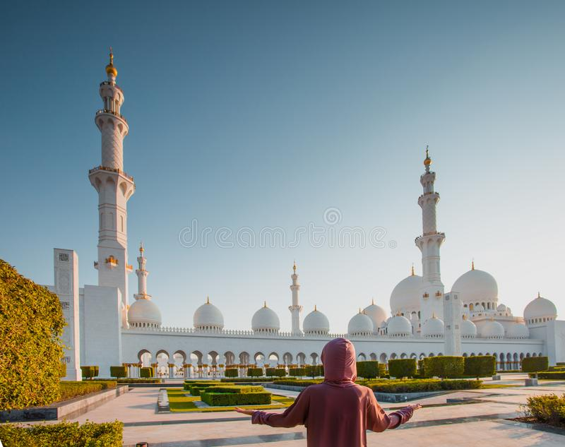 Mujer que se coloca en fondo de la mezquita imagen de archivo