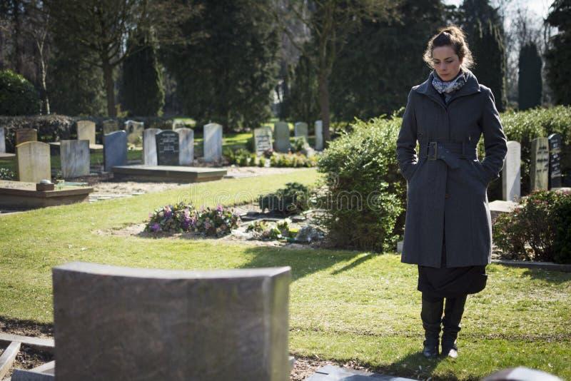 Mujer que se coloca en la lápida mortuaria imágenes de archivo libres de regalías