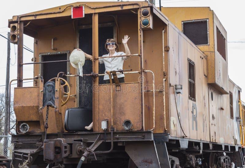 Mujer que se coloca en la parte de atrás de un tren que celebra su sombrero y agitar imagenes de archivo