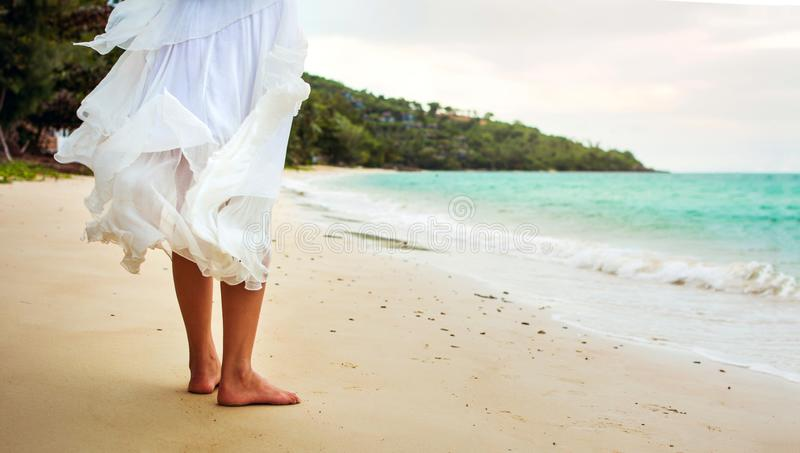 Mujer que se coloca en la playa en el vestido blanco foto de archivo