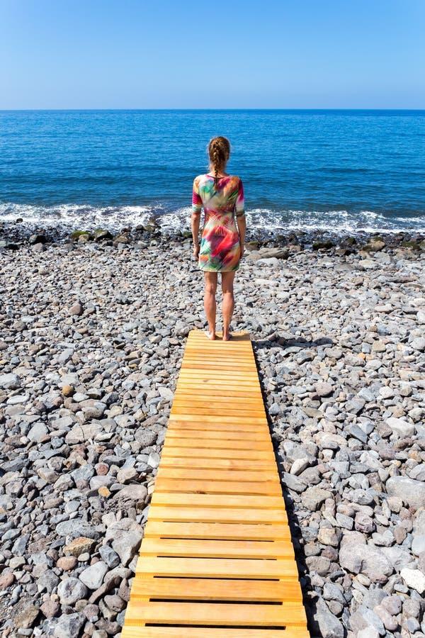 Mujer que se coloca en la trayectoria de madera en el mar imagen de archivo libre de regalías