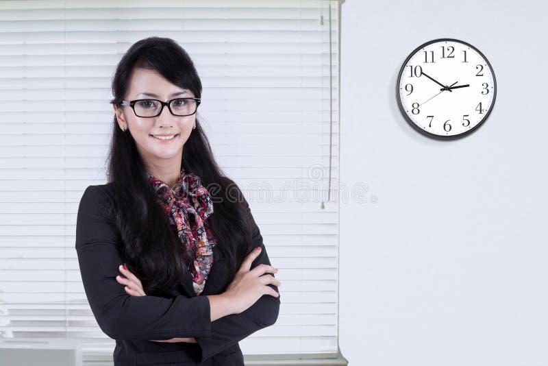 Mujer que se coloca en oficina con el reloj en la pared fotografía de archivo
