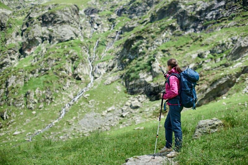 Mujer que se coloca en piedra en el pie de las montañas de Fagaras imagenes de archivo