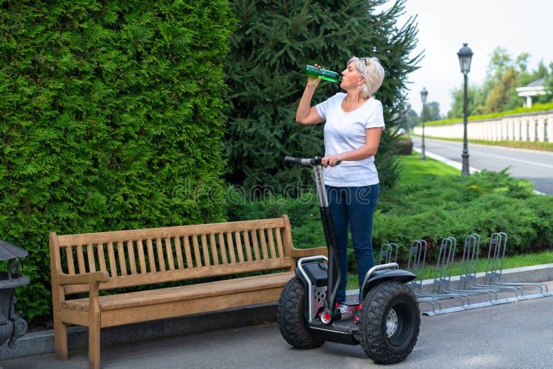 Mujer que se coloca en transportador personal rodado foto de archivo libre de regalías