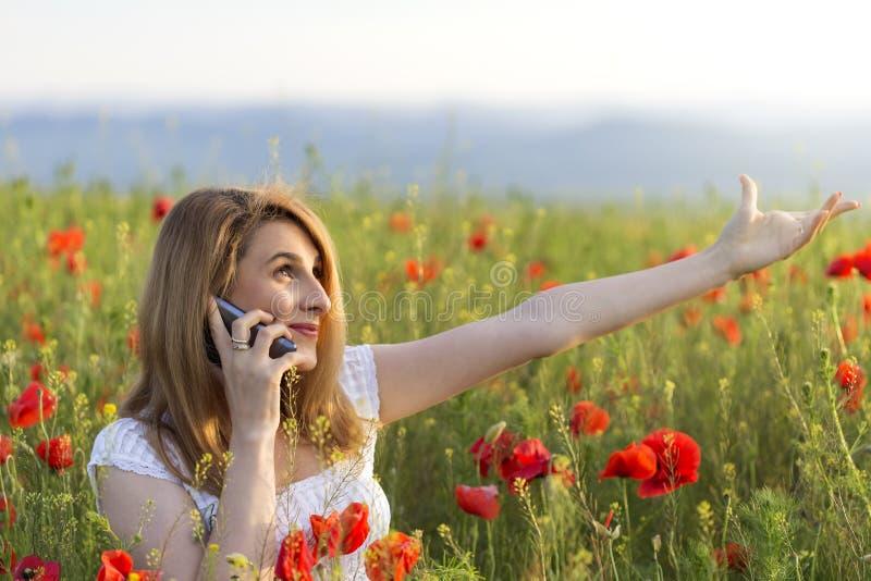 Mujer que se coloca en un campo de la amapola que habla en su teléfono fotos de archivo