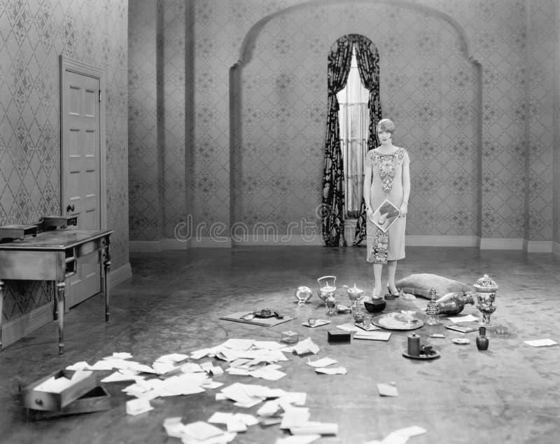 Mujer que se coloca en un cuarto vacío dispersado con las letras (todas las personas representadas no son vivas más largo y ningú foto de archivo libre de regalías