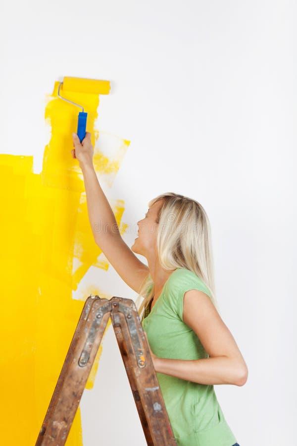 Mujer que se coloca en una pintura de la escalera foto de archivo libre de regalías